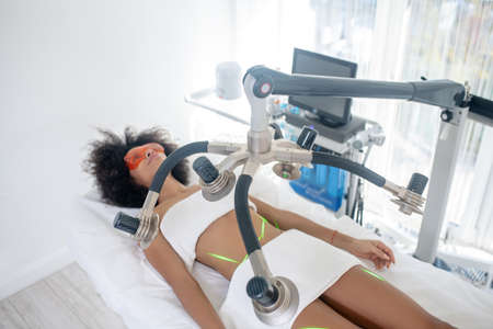 Cosmetology, laser. Young slim woman reclining on daybed receiving green laser procedure in cosmetology office Reklamní fotografie