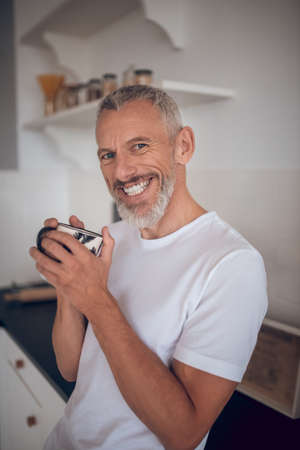 Good mood. Grey-haired tall man holding a cup and smiling nicely