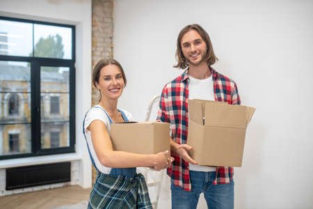 Moving. Young man and woman standing near the wall with card boards in hands