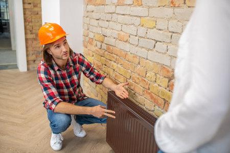 Some blemishes. Construction worker in orange helmet explaining something to a customer