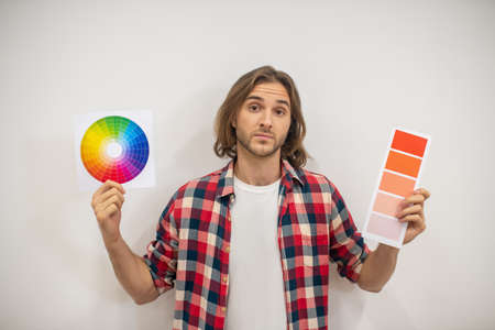 Hard choice. Young man holding color palette and looking uncertain