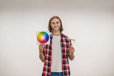 Painting. Young man holding a paint roller and a color palette