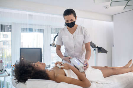 Cosmetological procedure. Young girl lying on couch with closed eyes and medic in protective mask during cosmetic procedure Banque d'images
