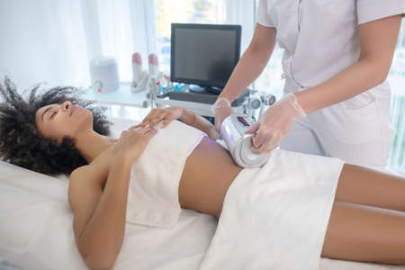 Cometological procedure. Young dark-haired girl calm with closed eyes lying on couch during cosmetic procedure