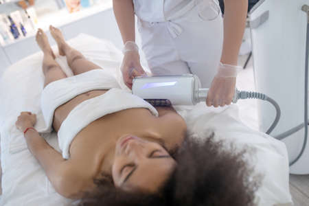 Cosmetology salon. Calmly lying young slender woman and hands of doctor doing cometic procedure Banque d'images