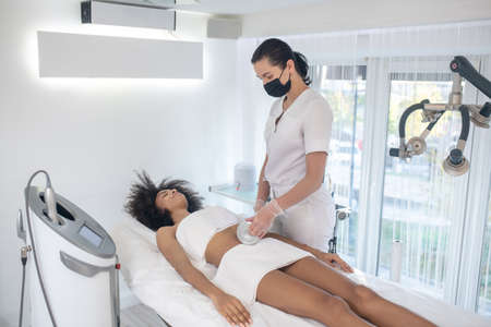 Cosmetology, bodycare. Woman beautician in protective mask with electronic device in her hands doing cosmetic procedure to young girl Banque d'images
