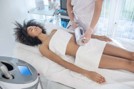 Bodycare, positive emotion. Smiling young woman lying in beauty parlor during medical body care procedure Banque d'images