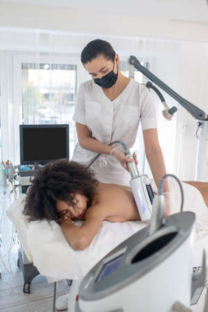 Effective cosmetology. Woman beautician standing over couch doing hardware procedure to girl lying on her stomach