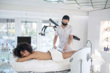 Treatment room. Woman beautician in black protective mask with device in her hands standing near couch and lying young girl