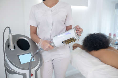 Hardware cosmetology. Doctor holding an apparatus for aesthetic body correction while standing near patient lying on daybed