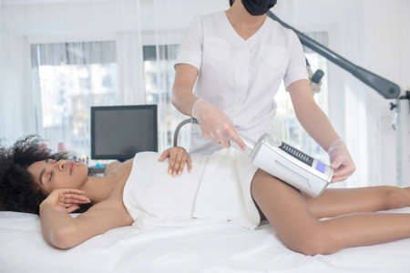 Problem area. Cosmetological procedure in problem area of thigh of girl lying on couch in beauty center