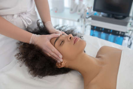 Cosmetological procedure. Hands of beautician in gloves on face of mulatto girl lying on couch