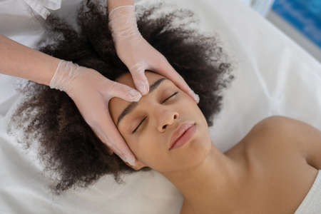 Complete relaxation. Calm face of young girl with closed eyes close-up and hands of doctor beautician
