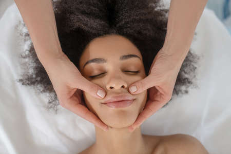 Facial massage. Beautician hands on face of young mulatto girl with closed eyes in beauty center
