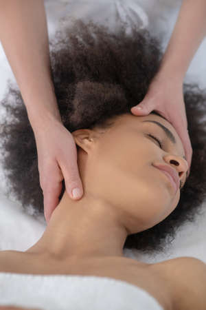 Mechanical facial massage. Beautician doctor hands massaging relaxed forehead and nape of young mulatto girl
