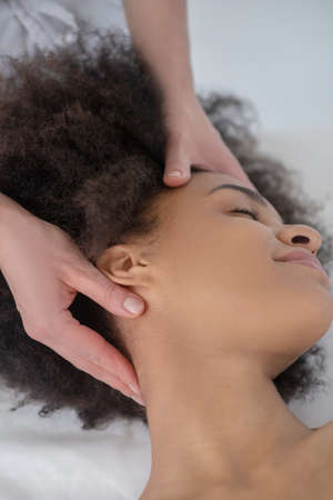 Neck massage. Hands of beautician pointwise massaging neck of relaxed young woman lying with closed eyes Banque d'images