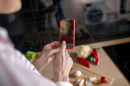 Recipes online. Woman standing in the kitchen and looking for recipes online