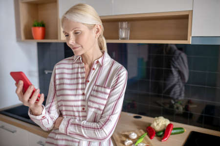 New recipes. Housewife standing in the kitchen and looking for recipes online Banque d'images