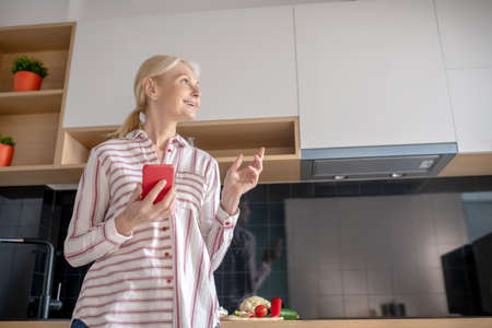 Thinking. Woman standing in the kitchen with a smartphone in hand and looking thoughtful Banque d'images