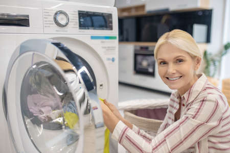 Housework. Blonde woman putting clothes into washing machine and smiling