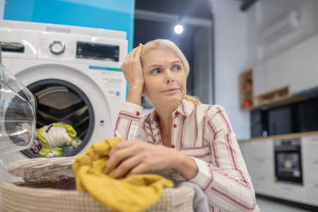 Thoughtful. Blonde woman sitting near washing machine and looking thoughtful Banque d'images