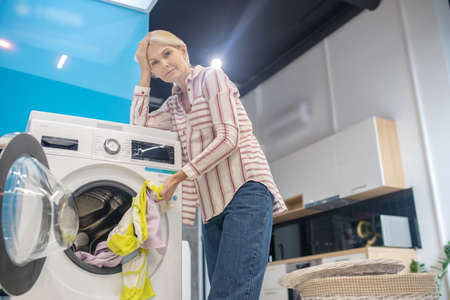 Housework. Blonde woman standing near washing machine an looking tired Banque d'images