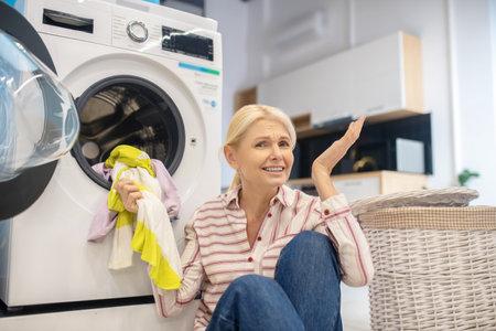 Housewife. Blonde housewife in striped shirt sitting near the washing machine