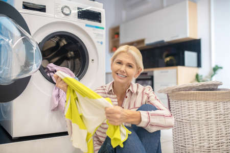 Housewife. Blonde housewife in striped shirt and jeans sitting near the washing machine