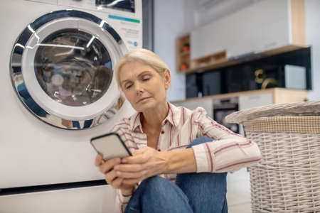 Online. Blonde housewife in striped shirt sitting near the washing machine and reading something online Banque d'images