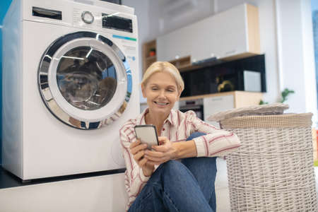 Housewife. Blonde housewife in striped shirt sitting near the washing machine and holding a smartphone Banque d'images