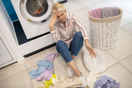Housewife. Blonde housewife in striped shirt sitting near the washing machine and feeling tired Banque d'images