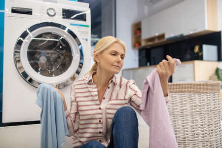Washing. Blonde housewife in striped shirt sitting near the washing machine with plenty of clothes