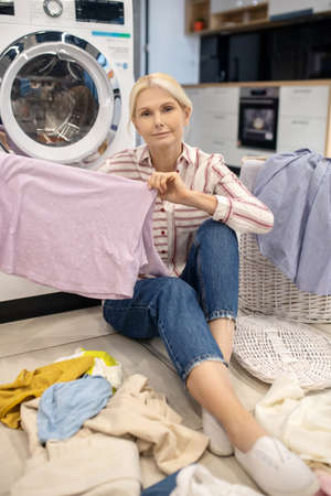 Clean clothes. Blonde housewife in striped shirt sitting near the washing machine and holding clothes