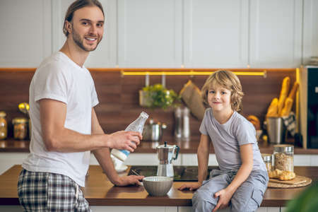 In the kitchen. Young man in homewear and his son having breakfast
