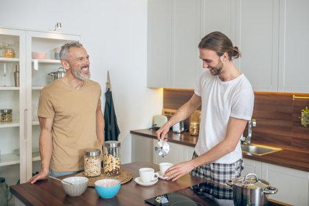 Together. Lgbt couple having breakfast together at home