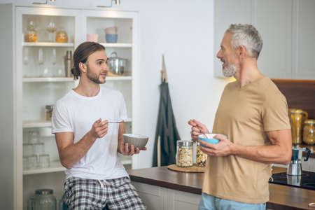 Coffee together. Smiling couple having coffee and talking in the kitchen