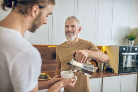 Morning coffee. Couple having coffee together at home and feeling good
