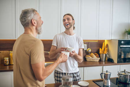 Morning together. Smiling couple having breakfast together at home and feeling good