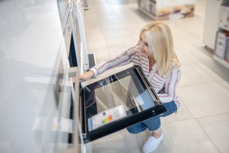 In a store. Blonde woman choosing oven in a megastore