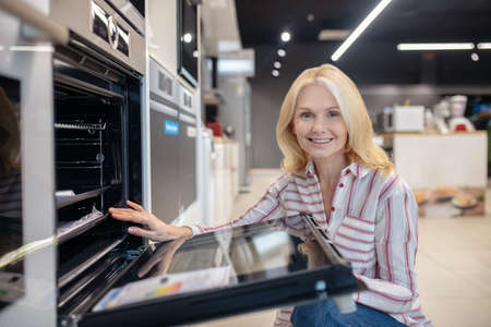 Goods for home. Blonde customer choosing oven in a showroom and smiling Banque d'images
