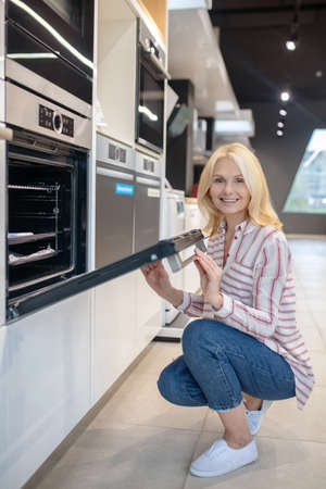 New oven. Blonde customer choosing oven in a showroom and looking contented