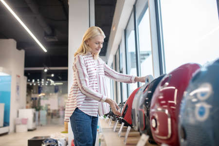 New model. Blonde customer choosing a vaccum-cleaner in a showroom