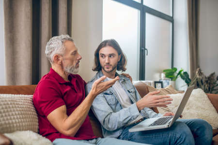 Two men. Two men sitting next to each other and watching something on laptop Stockfoto