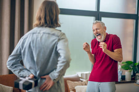 Happy man. Grey-haired man looking happy receiving a gift from his partner