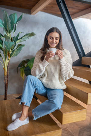 Day at home. Young dark-haired pretty woman in jeans and white sweater sitting on stairs