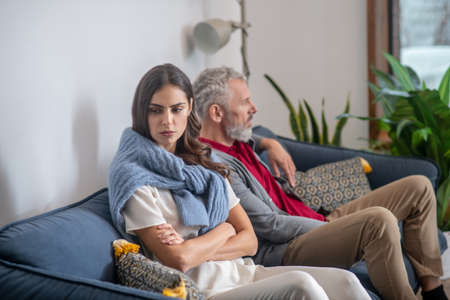 Family relations. A young woman and bearded man sitting on a sofa