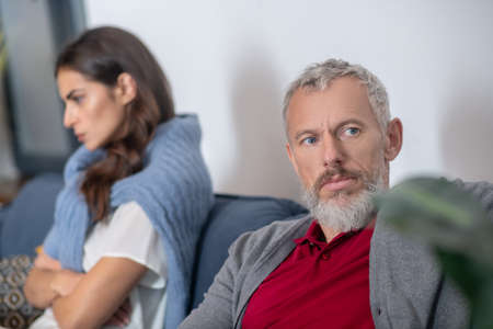 Disagreement. A disappointed bearded man sitting near his wife