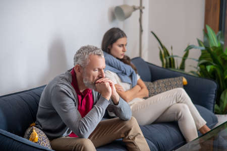 Thinking about relations. Thoughtful man sitting on a sofa near his wife
