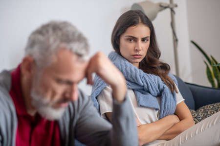 Family argument. A woman looking angrily on her grey-haired husband Stockfoto
