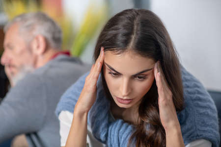 Health and relations. A young woman havinfg a headache as a result of argument